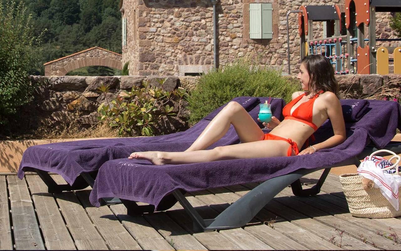 Femme sur un transat hôtel avec piscine sud de la france